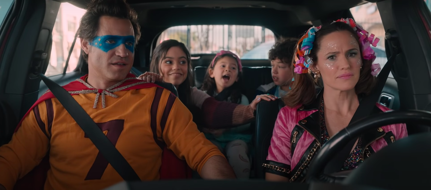 A family in superhero costumes in a car