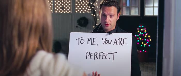 """The card guy from """"Love Actually"""" holding the card that says, """"To me, you are perfect"""""""