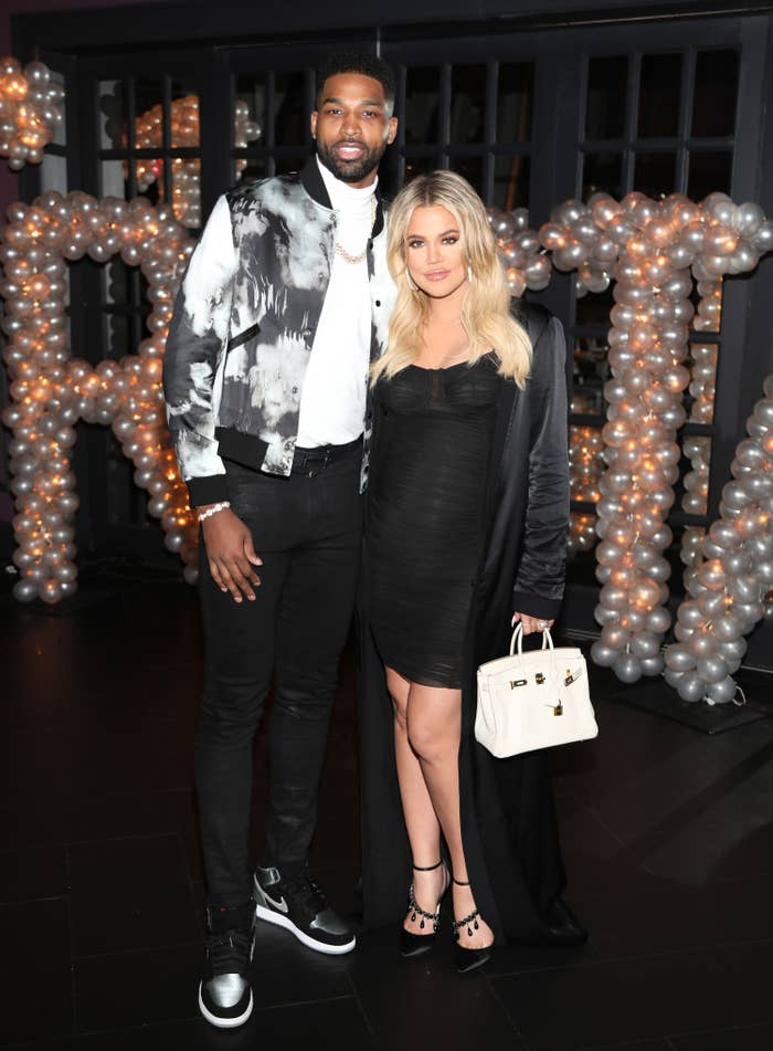 Tristan Thompson, in a black and white graphic vest with a white shirt and black pants, stands next to Khloe Kardashian, in a black dress