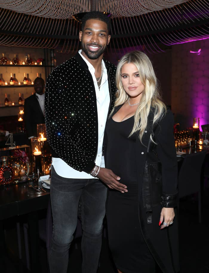 Thompson, in a sparkly jacket and black jeans, puts his hand on Khloe's belly at an event