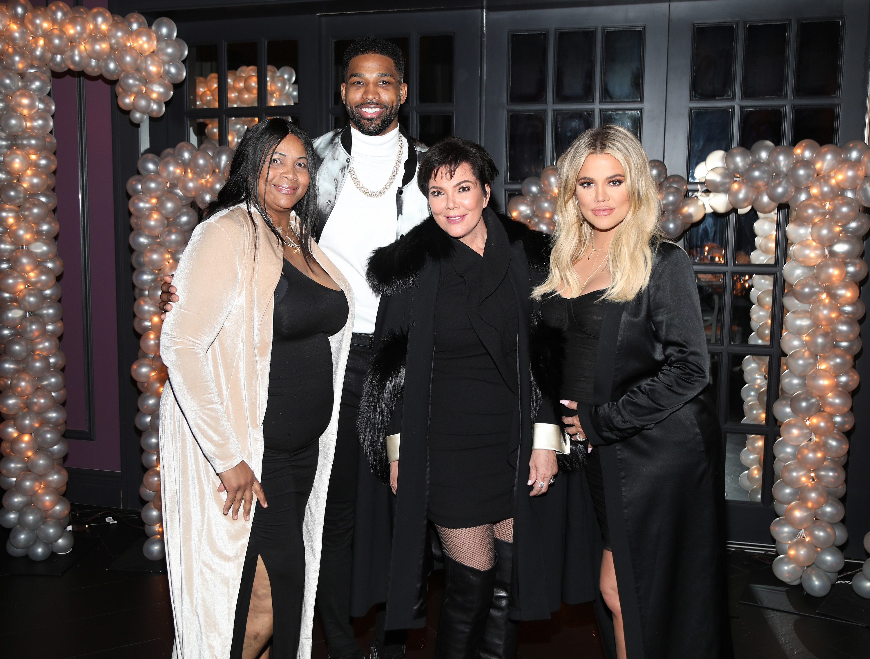 Andrea and Tristan Thompson and Khloe Kardashian and Kris Jenner all pose for a photo together at an event
