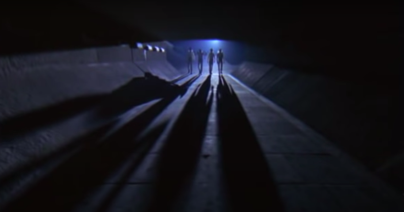 Four people walking in a tunnel