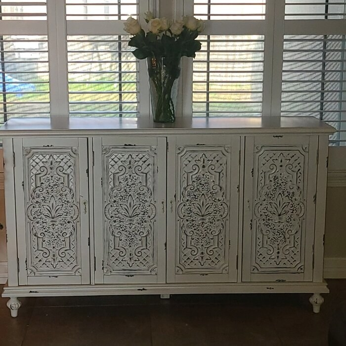 The credenza with a vase of white roses on top