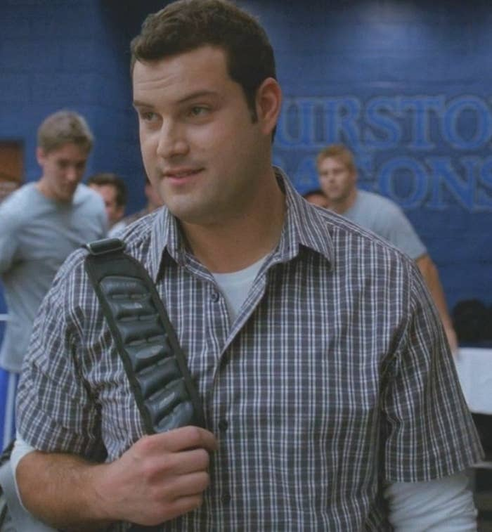 David Karofsky wears a blue and white checkered button up shirt over a long sleeve white shirt while holding the backpack strap across his chest.