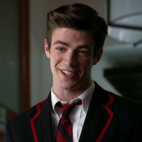 A close up ofSebastian Smythe as he wears a blue blazer with red lining and a matching striped tie.