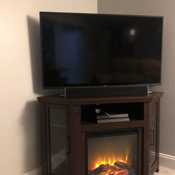 The corner TV stand with fireplace blaring and TV on top