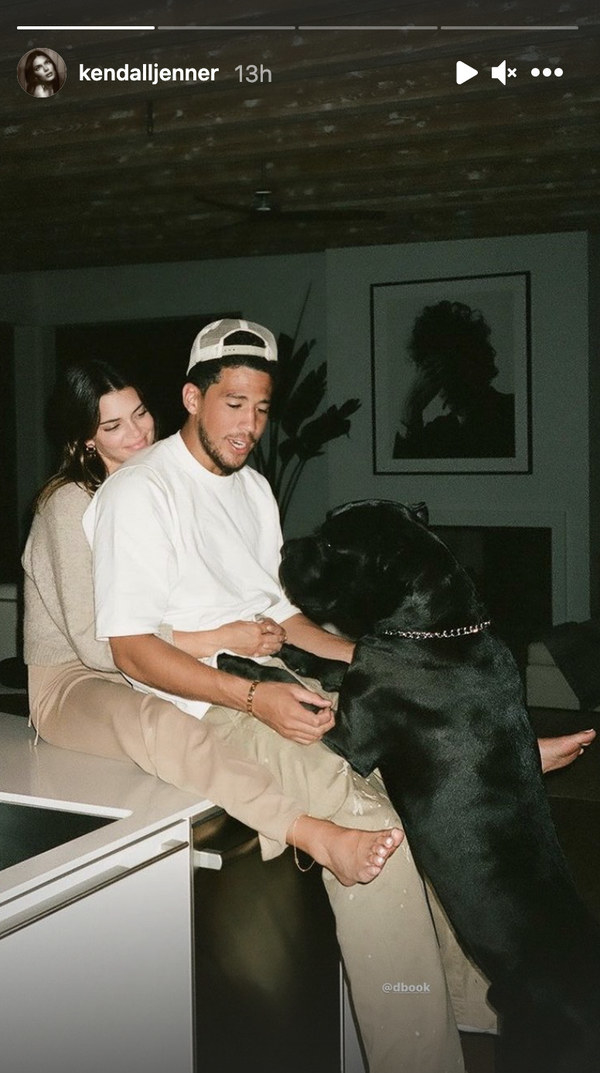 Kendall Jenner wraps her arms around Devin Booker's waist as his dog hops up on his lap