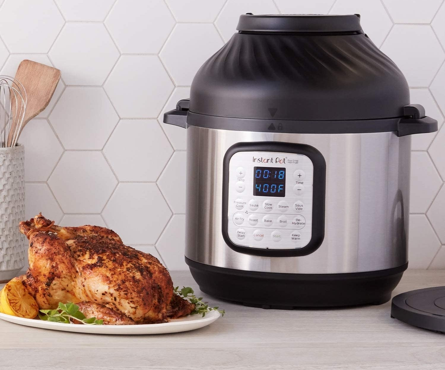 Silver and black instant pot with control panel next to a cooked chicken