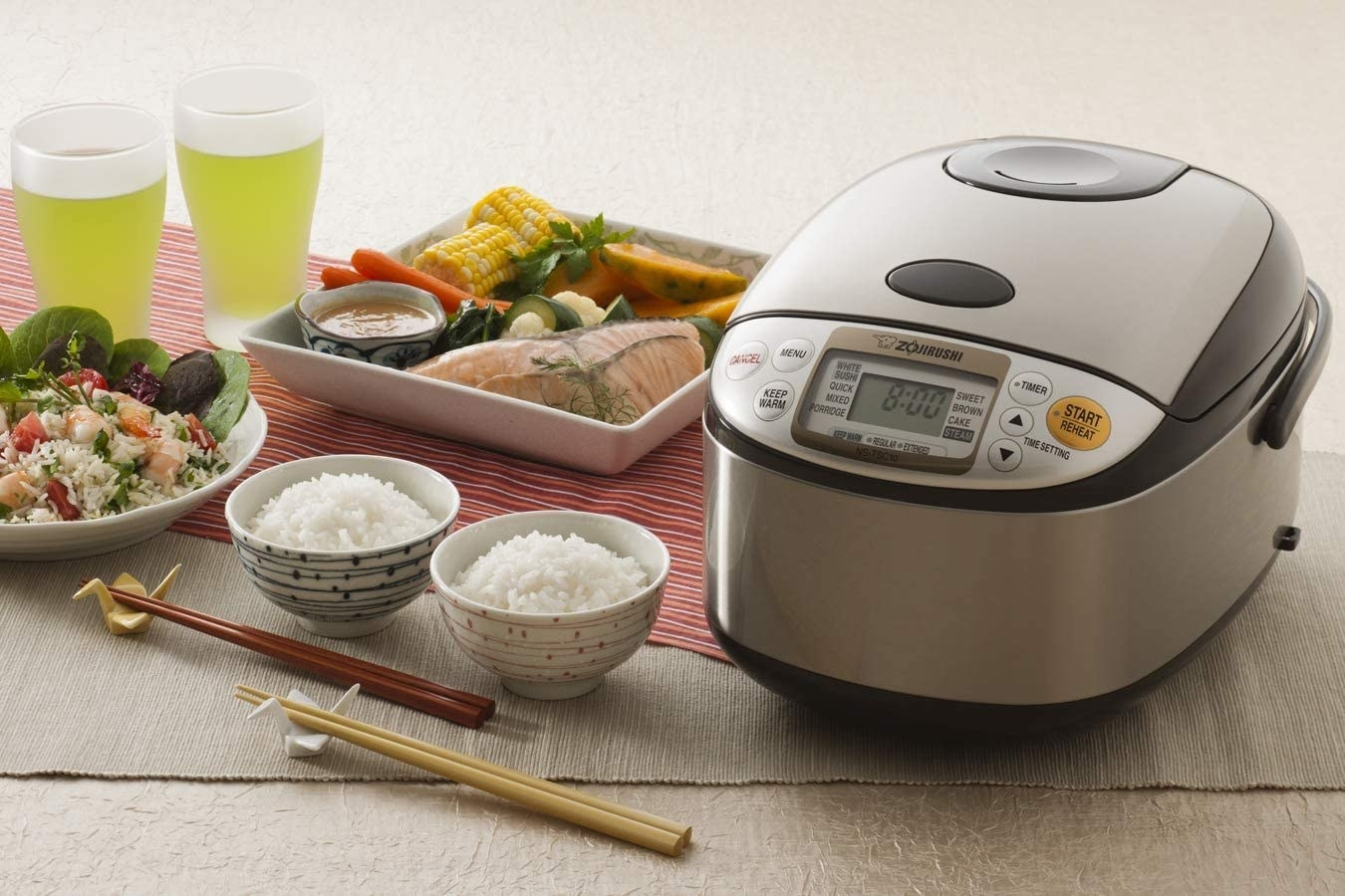 the rice cooker next to two bowls of rice and vegetables
