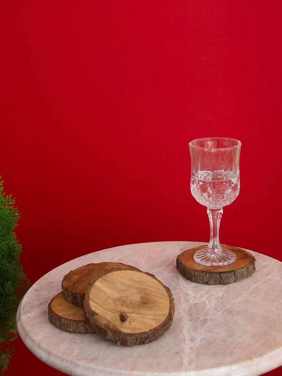 A glass atop a wooden coaster