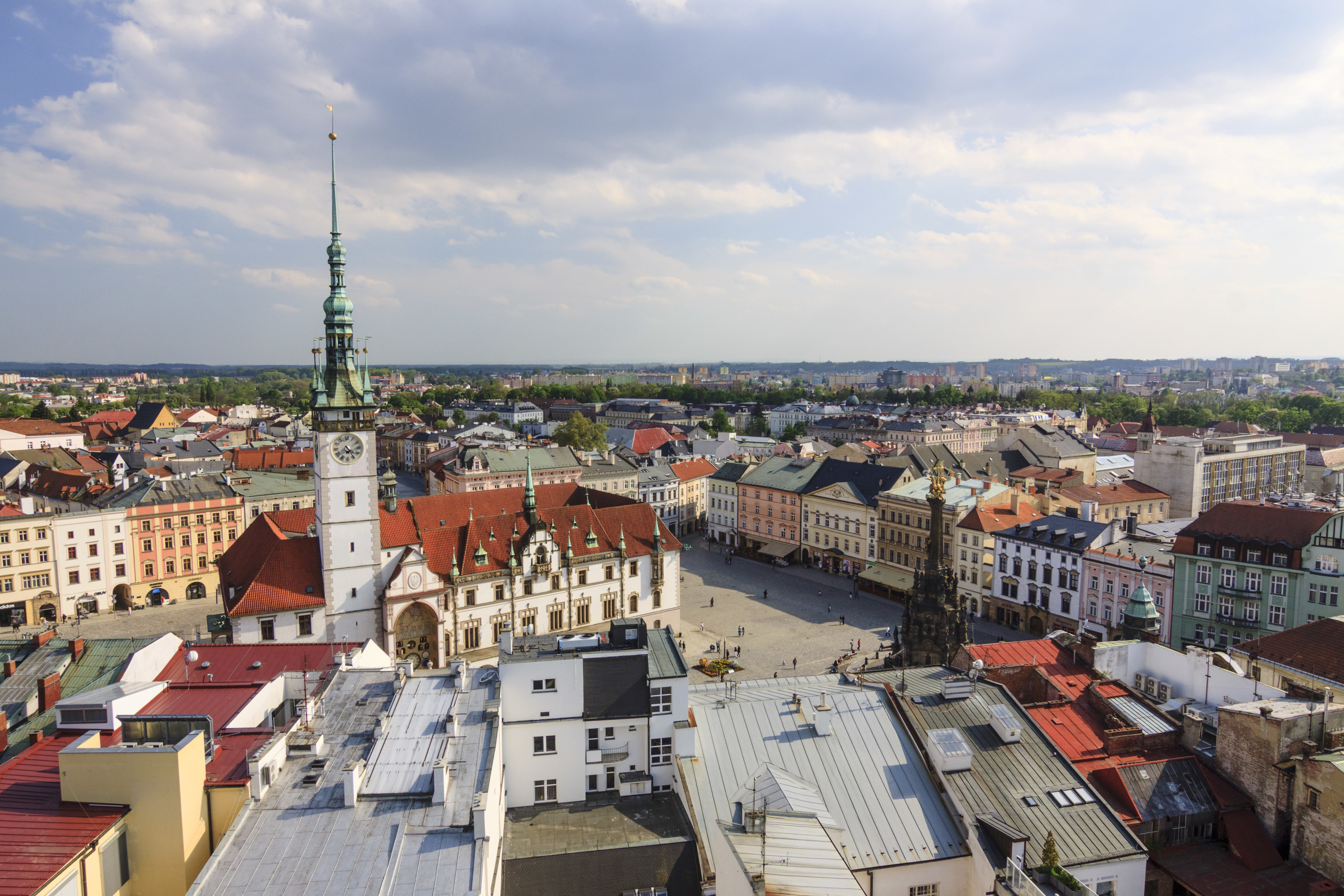 Aerial view of Olomouc, showing a grand plaza with various charming architecture on show.