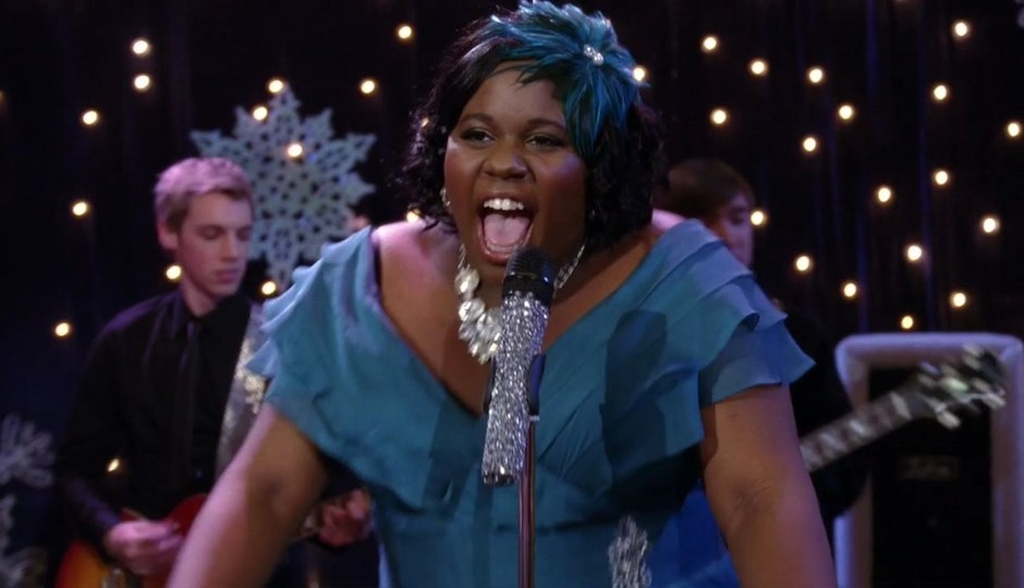 Unique Adams, wearing a v-neck blue ruffle dress with matching hair piece, sings into a bedazzled microphone in front of a live band.