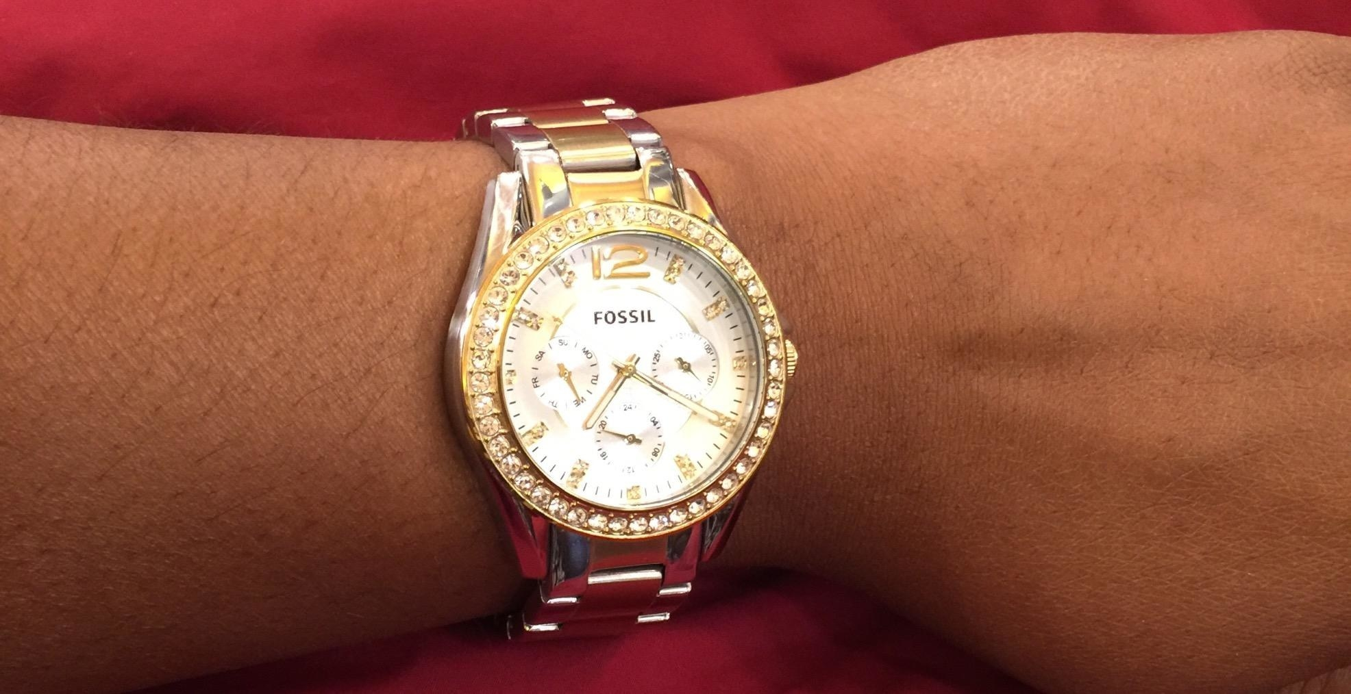 reviewer wearing gold and rhinestone fossil watch
