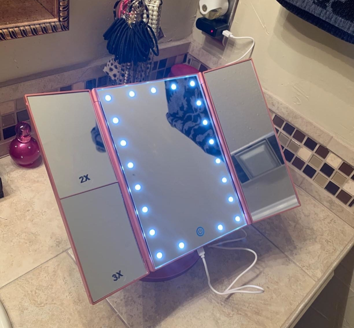 reviewer's lighted makeup mirror in pink on a bathroom counter