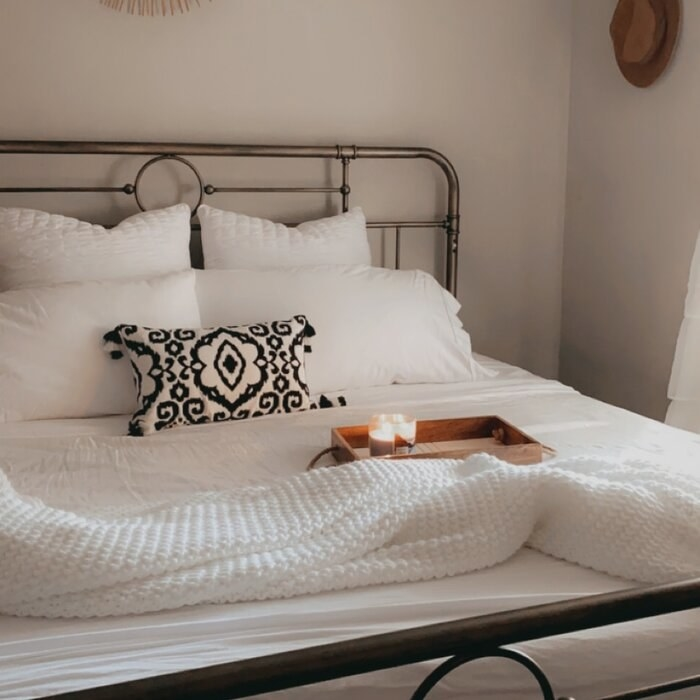 The bed frame made up with linens in a reviewer's home