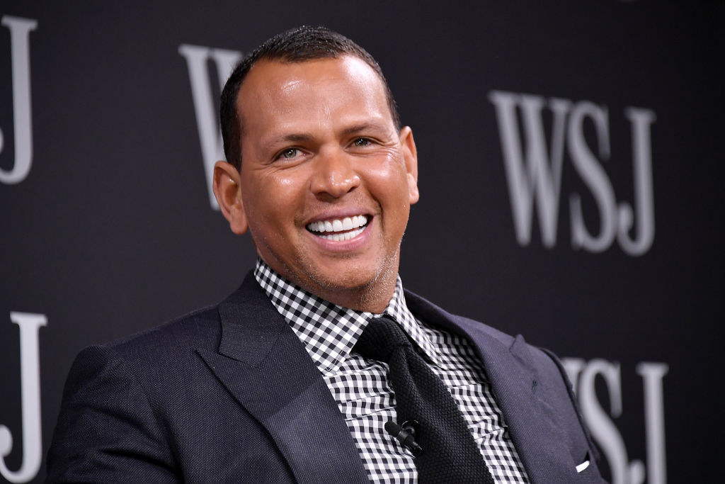 Alex Rodriguez smiles at the camera while attending a Wall Street Journal panel event.