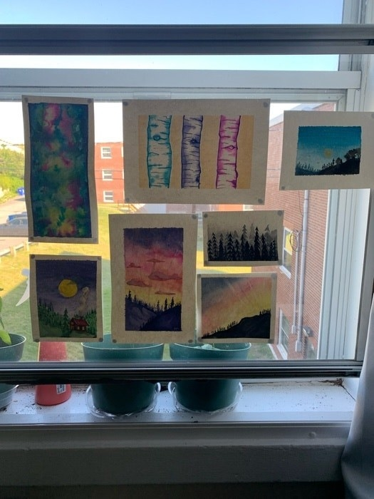 Seven watercolor paintings on white paper are taped to a clear window