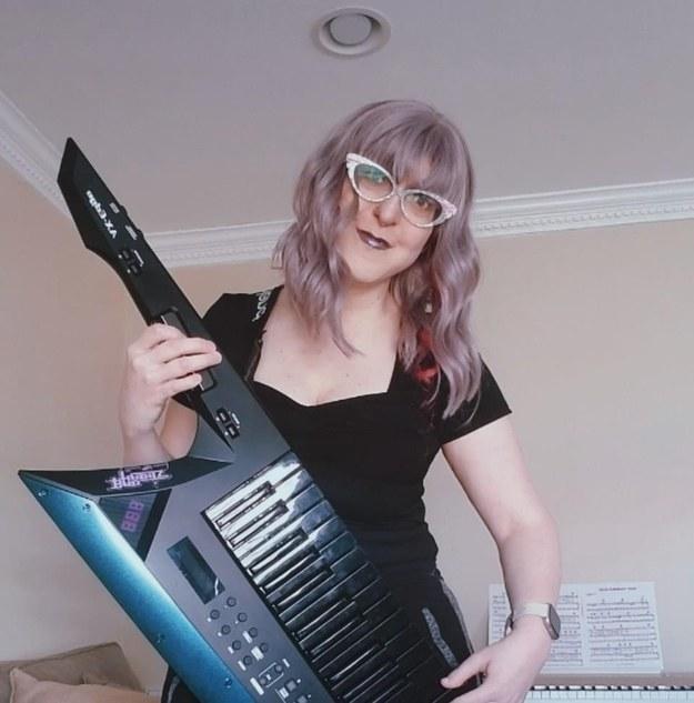 Woman plays keytar keyboard slung over her right shoulder