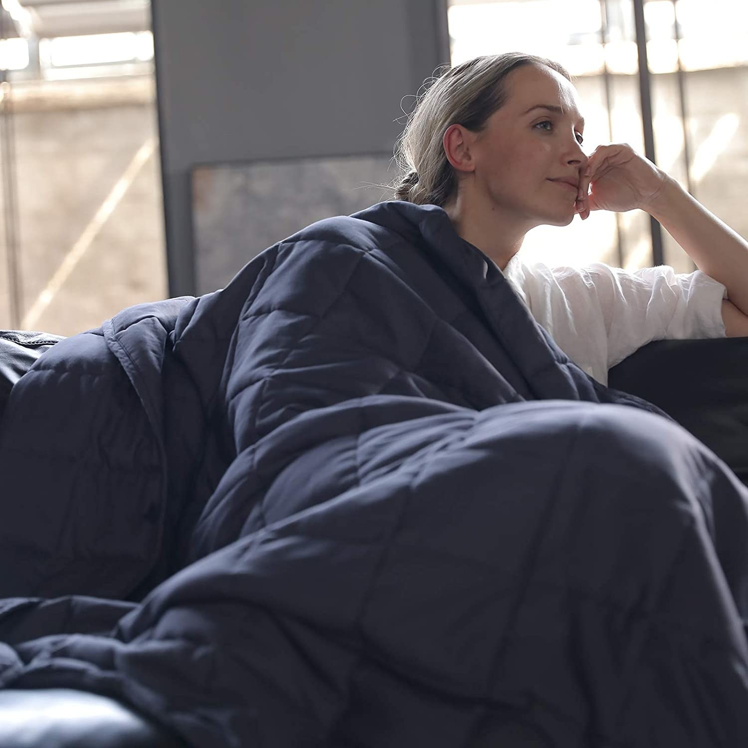 A woman sitting with a navy blue weighted blanket on her.