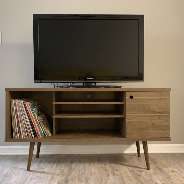 The TV stand with TV on top in a reviewer's home