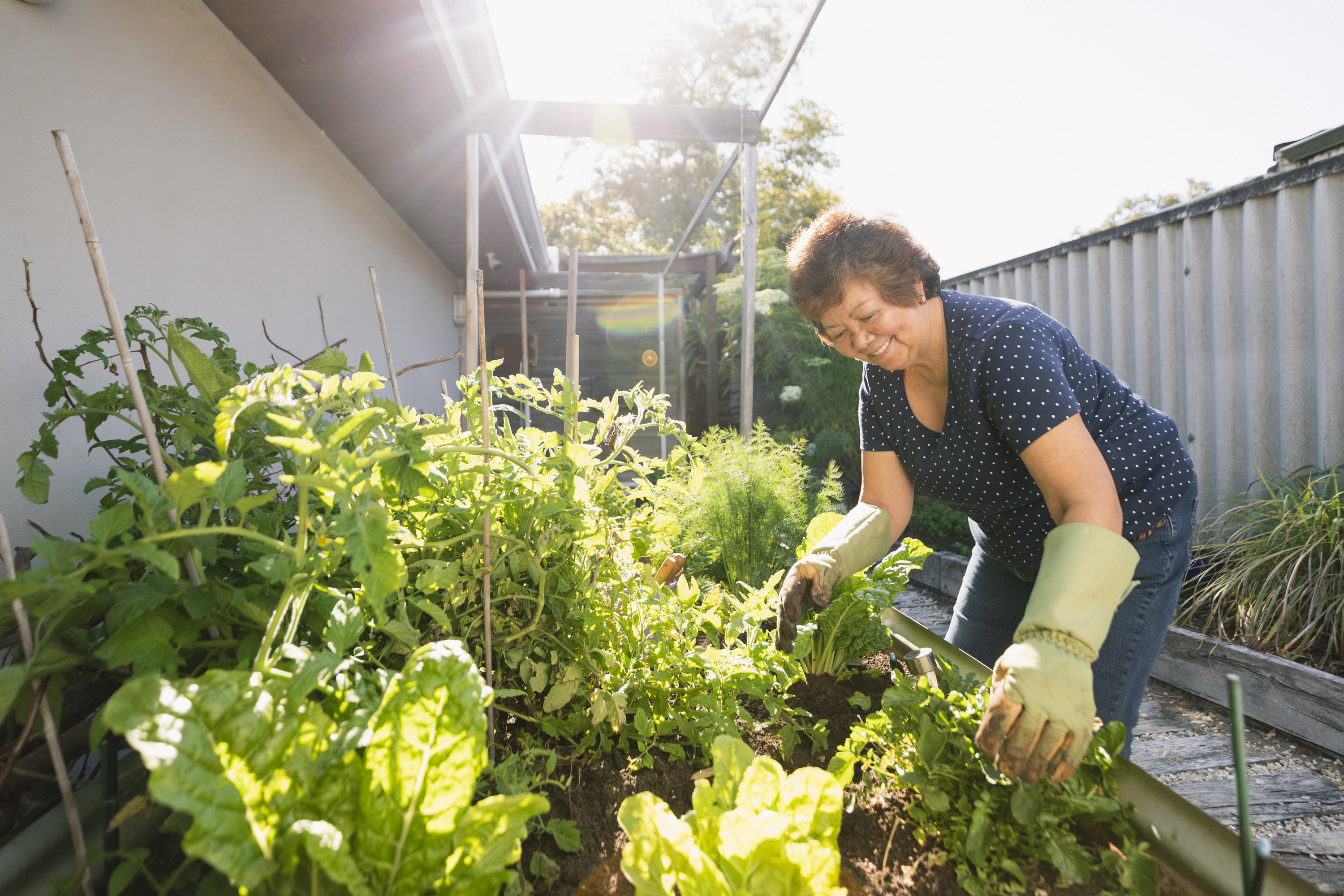 A smiling woman tends to her sunny outdoor garden