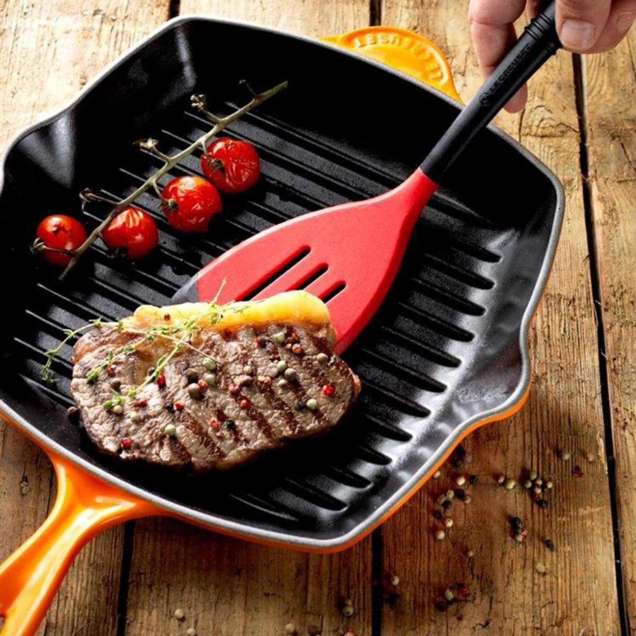 Hand flipping a steak that's grilling in an orange ridged square pan