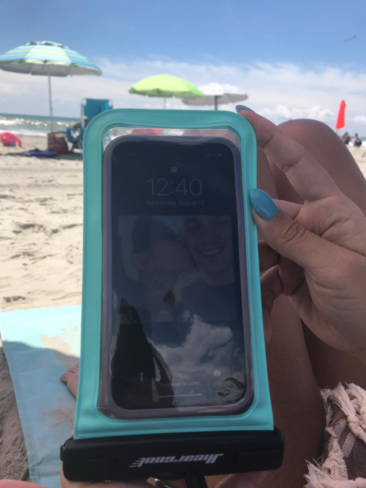 reviewer holding phone in teal case