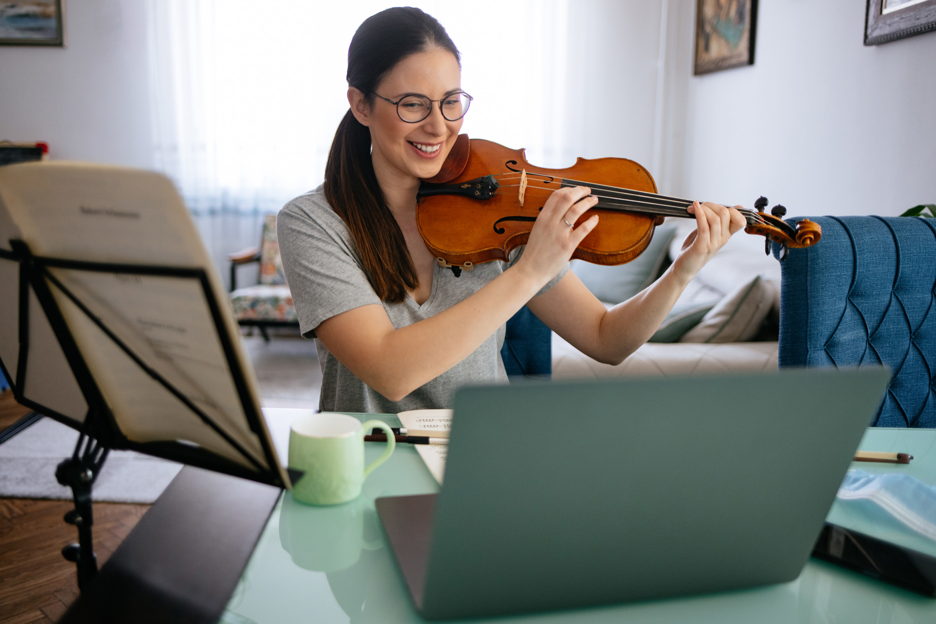 Woman smiles, while playing the violin in front of her laptop