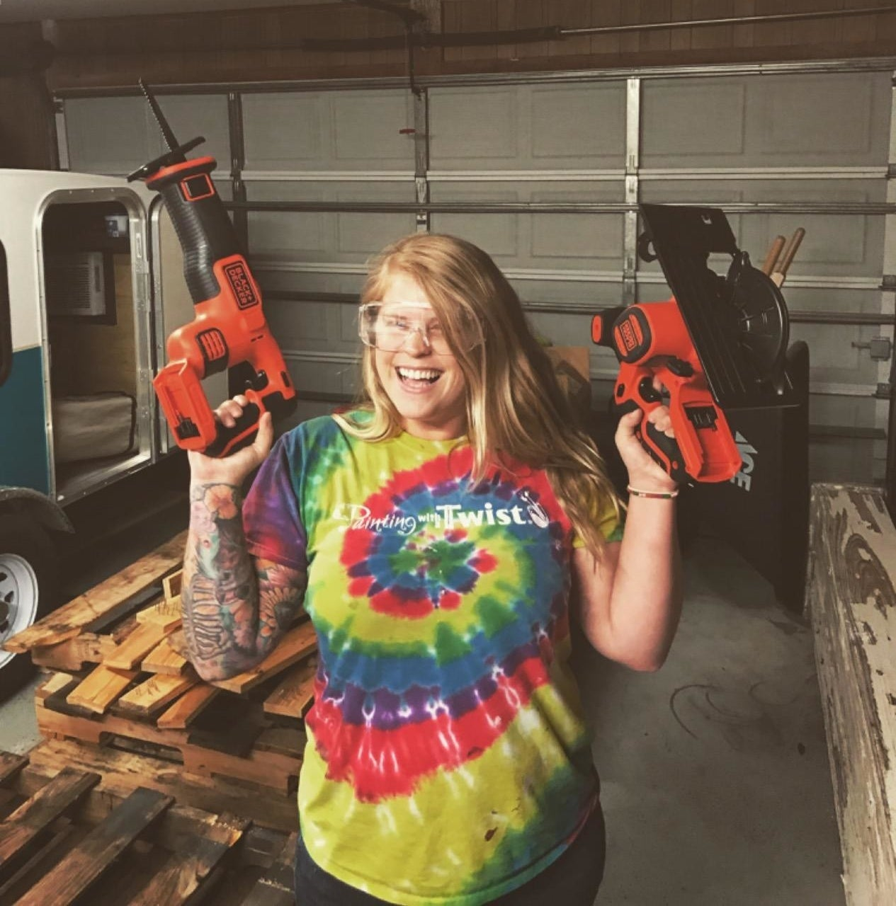 Reviewer is holding two power tools in each hand while smiling