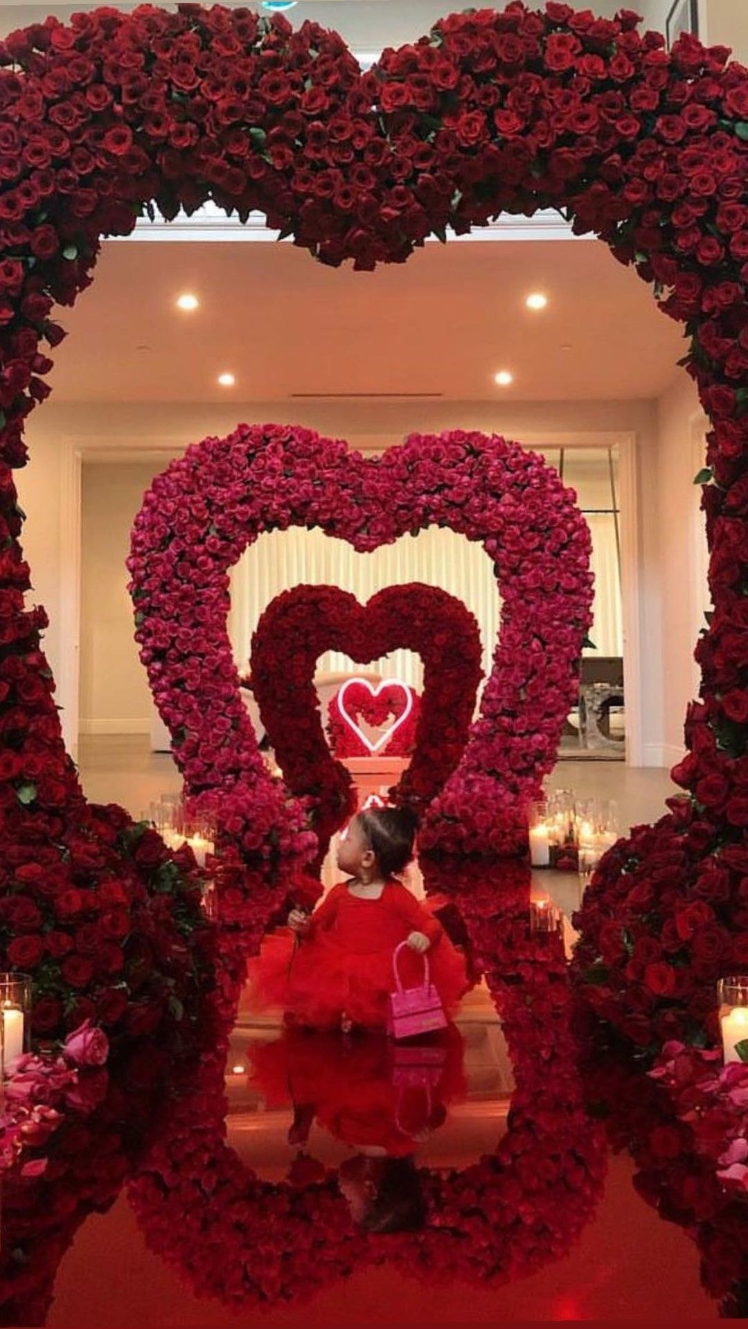 Stormi standing under one of multiple hearts shaped out of roses