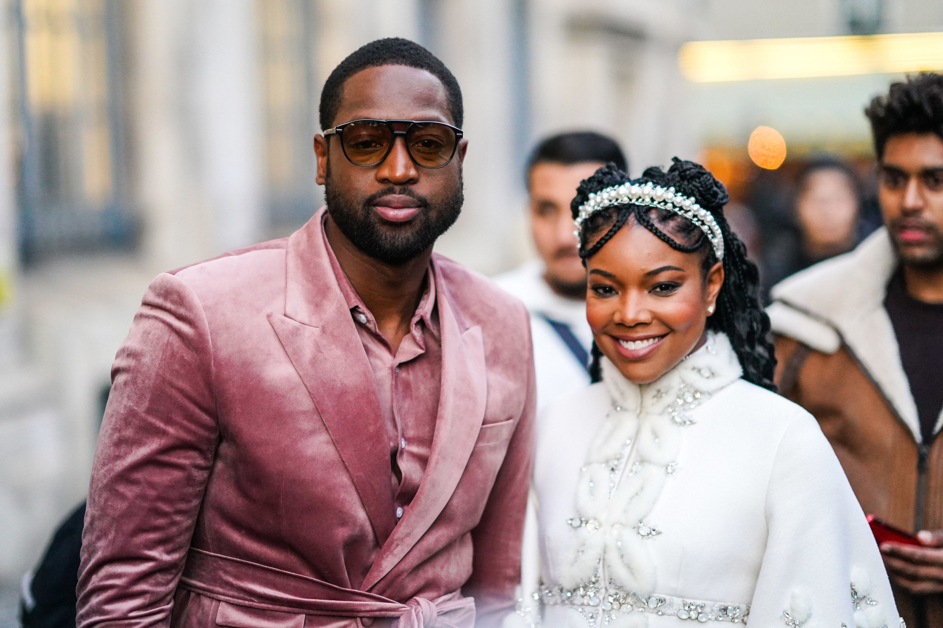 Dwayne Wade wears sunglasses, a velvet shirt, a velvet jacket, a matched belt, Gabrielle Union wears a pearl headband, a white fluffy jacket with rhinestone embroideries, a mandarin collar and bell sleeves, outside Ralph & Russo, during Paris Fashion Week