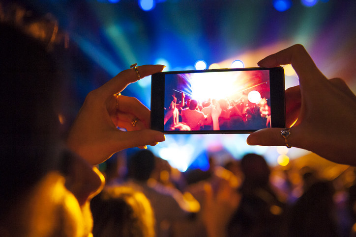 Person holding up their phone at a concert