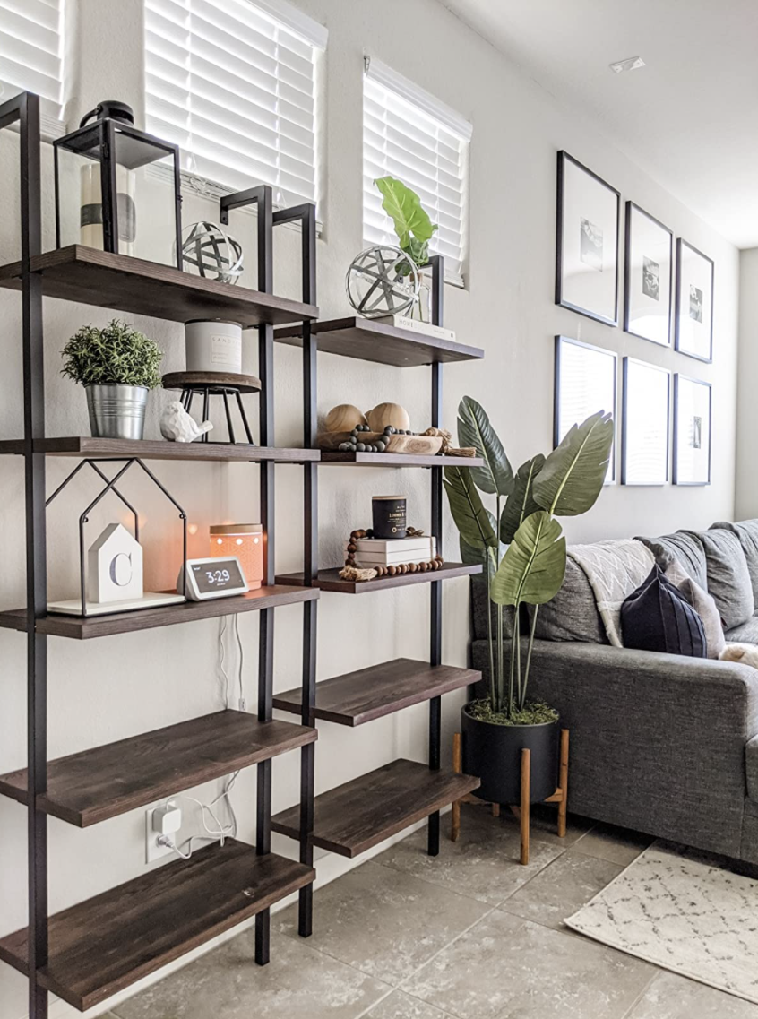 Two of the ladder shelves in brown and black are next to each other
