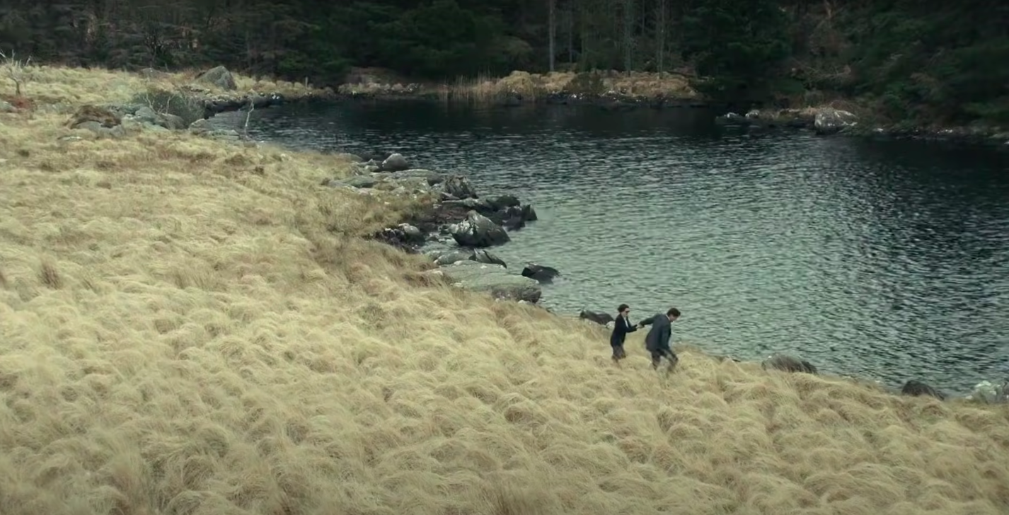 Two people walking near a lake