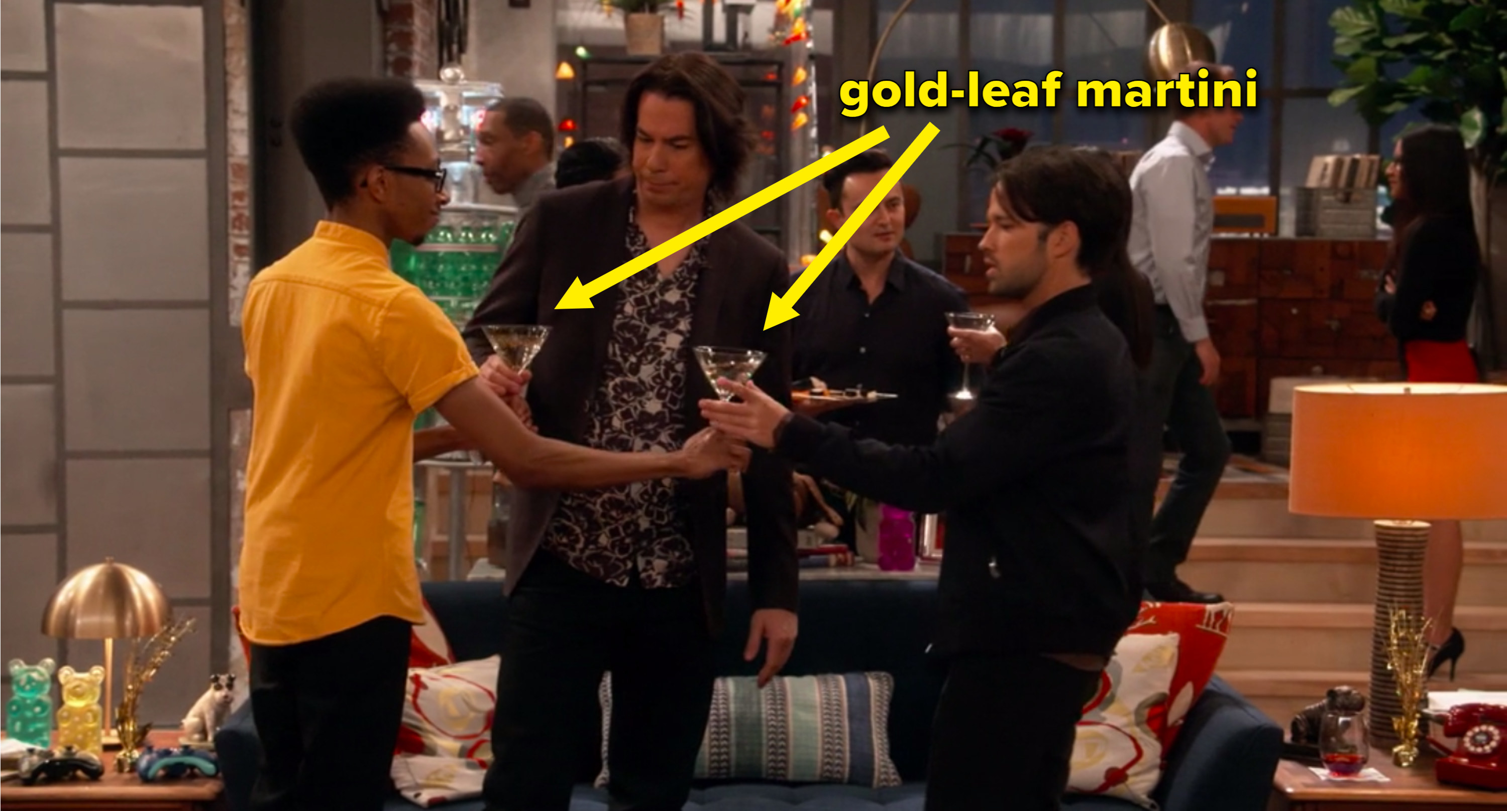 Spencer toasting gold leaf martinis with two people at his house party