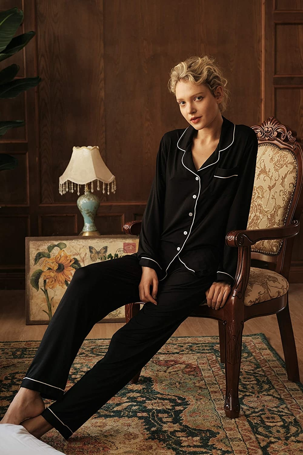 A model wearing the pajamas in black with white piping