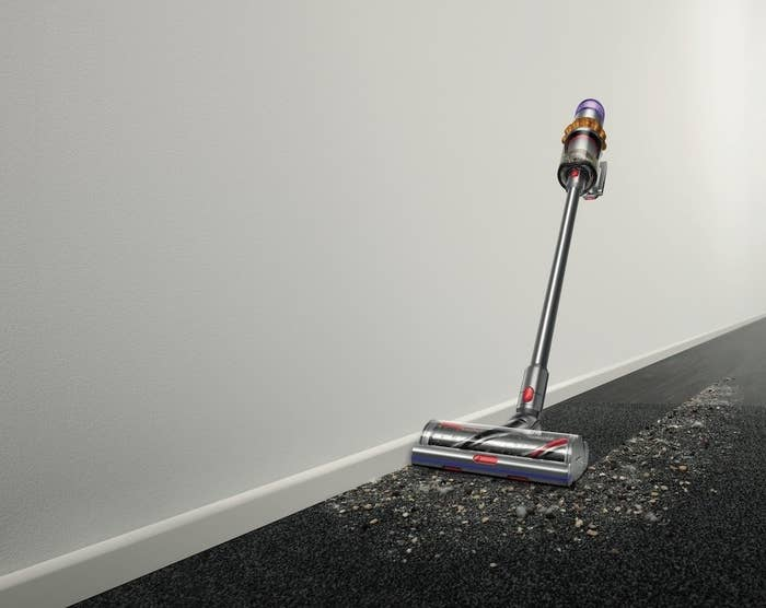 the silver dyson vacuum with purple and orange accents