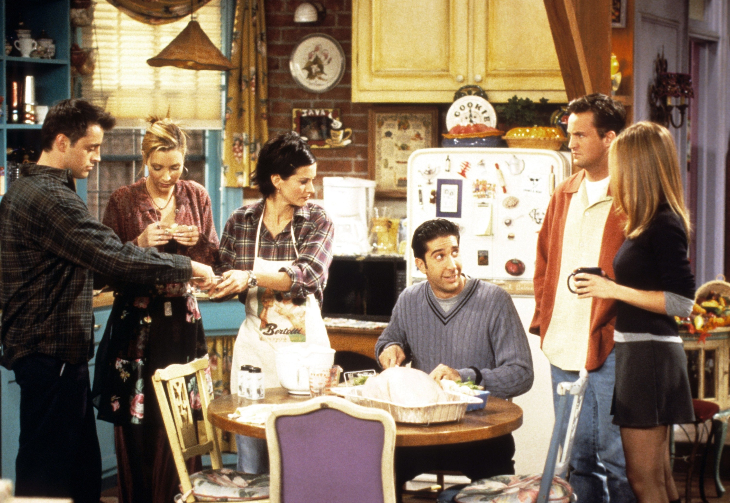Cast of Friends in the kitchen chatting