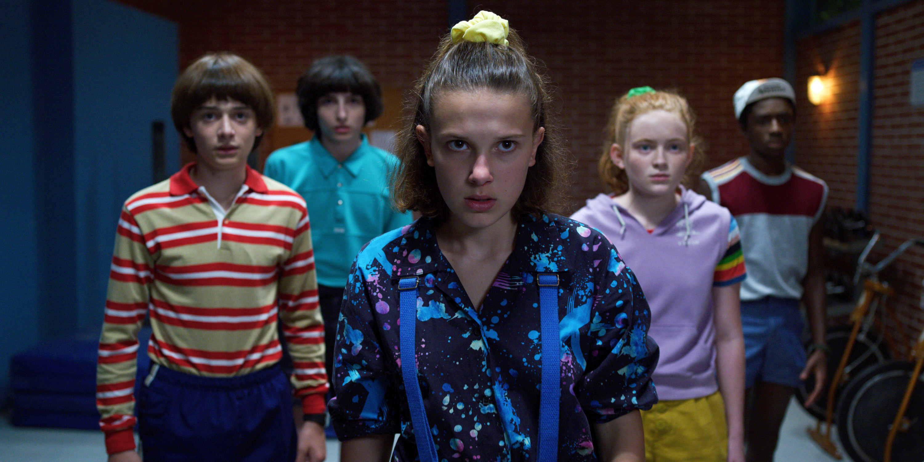 Kids of stranger things standing behind Eleven