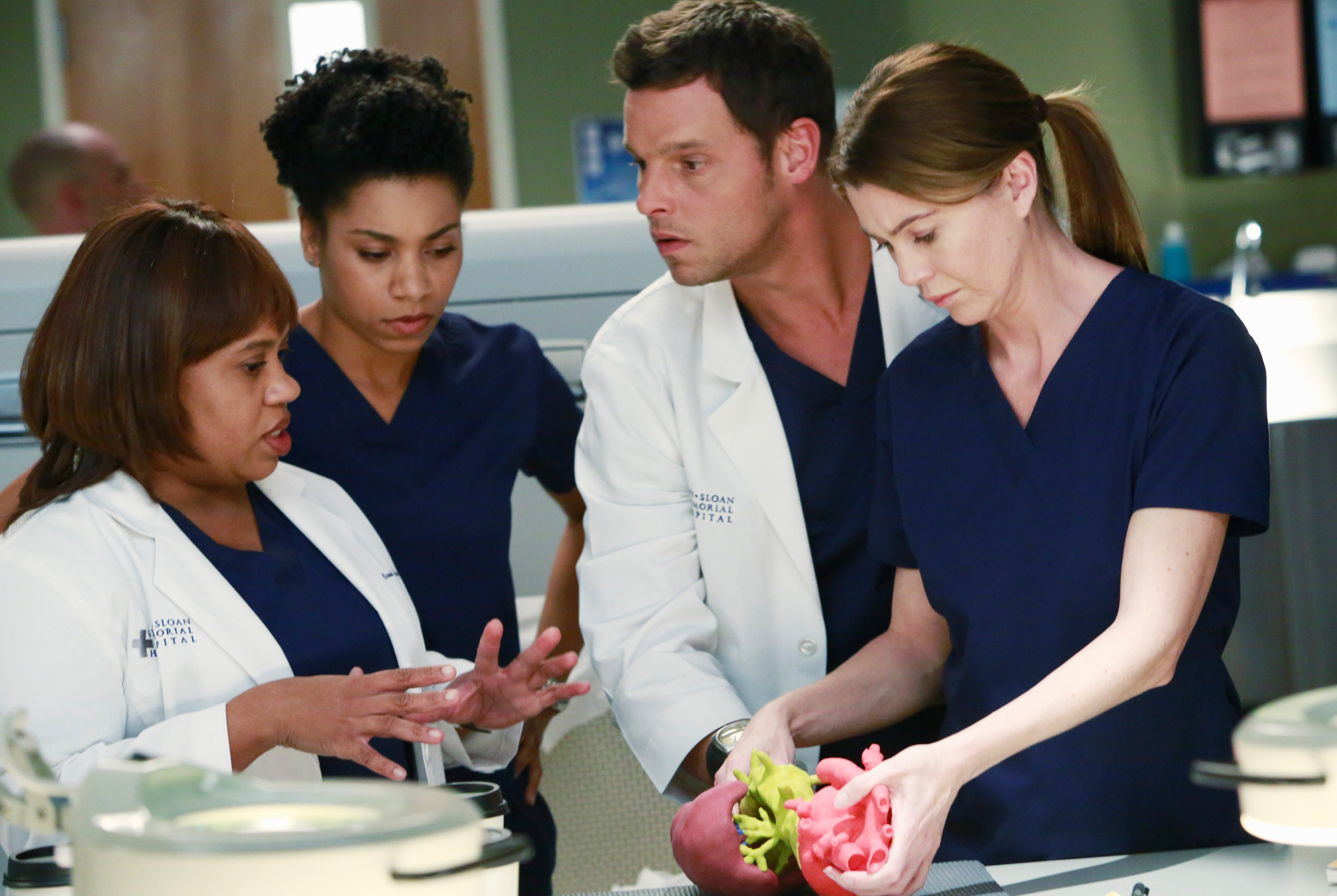 four characters of grey's anatomy huddled and chatting