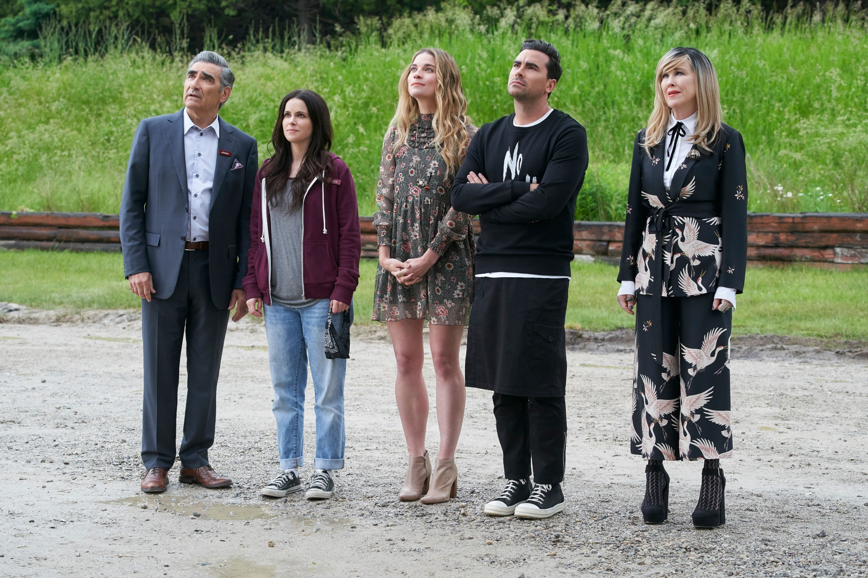 Cast of Schitt's Creek standing together and looking up