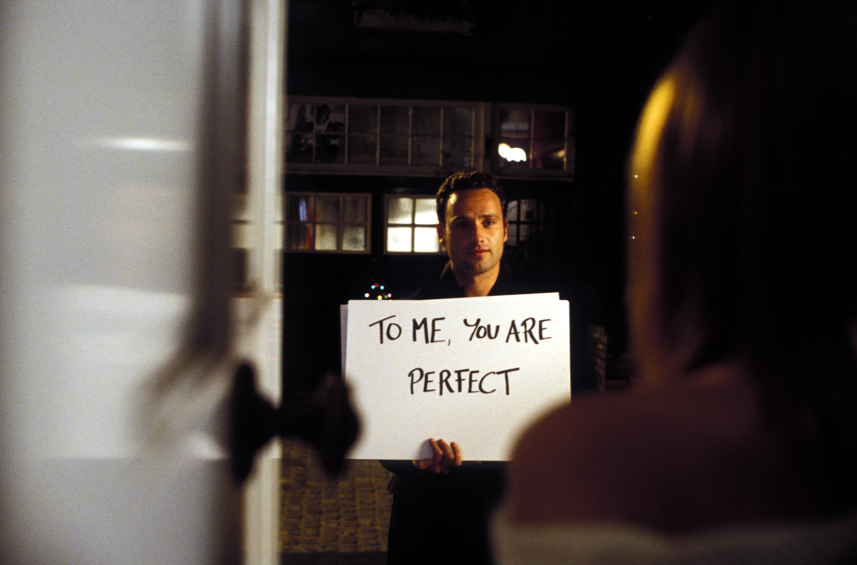 """Man holding card that says, """"to me you are perfect"""""""