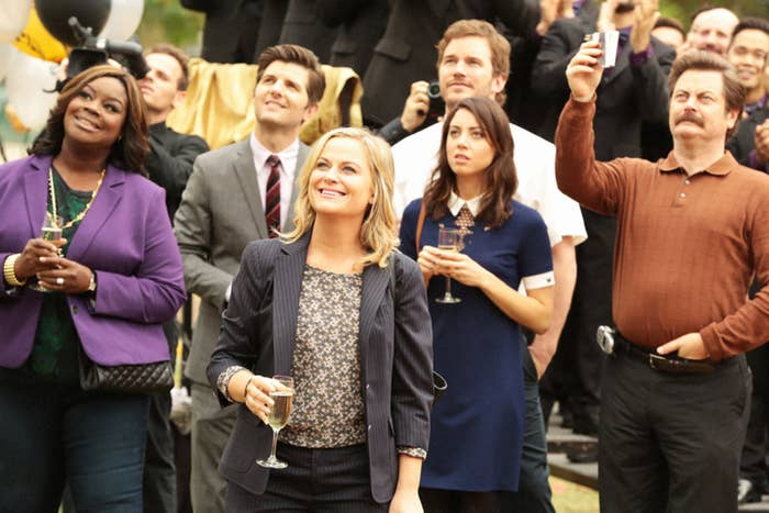 Cast of Parks and Rec looking up and smiling with champagne