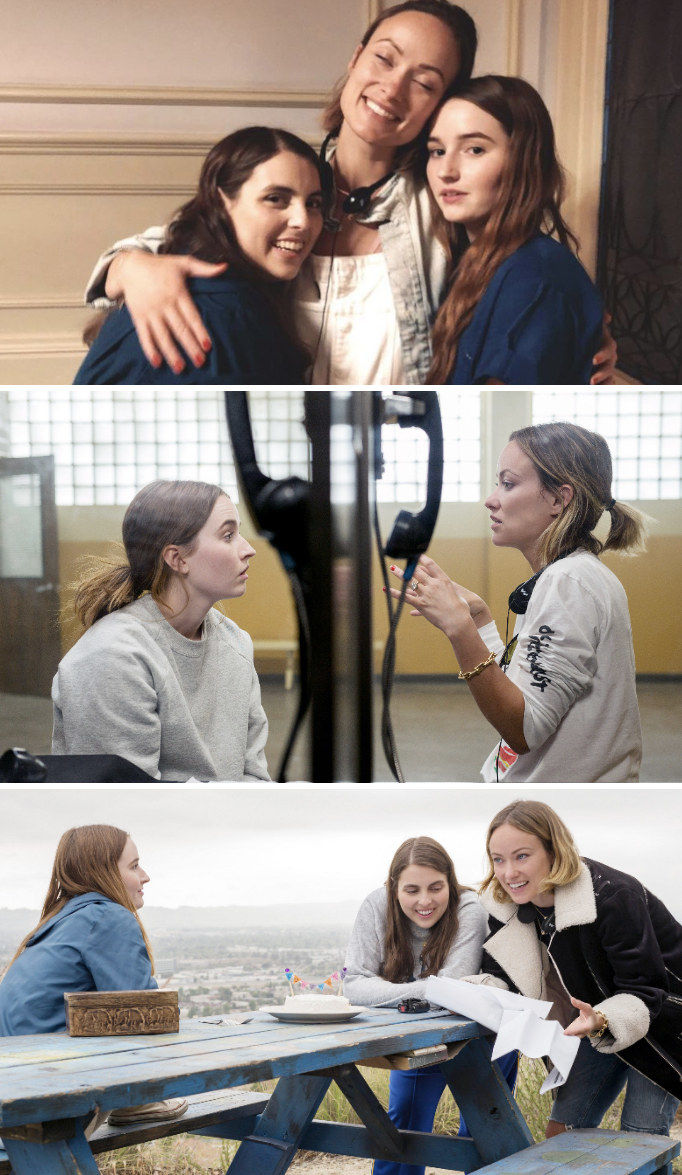 """Wilde posing with Beanie Feldstein andKaitlyn Dever behind the scenes of """"Booksmart;"""" Wilde directing Dever in jail;"""" Wilde directing Feldstein and Dever at a park bench"""