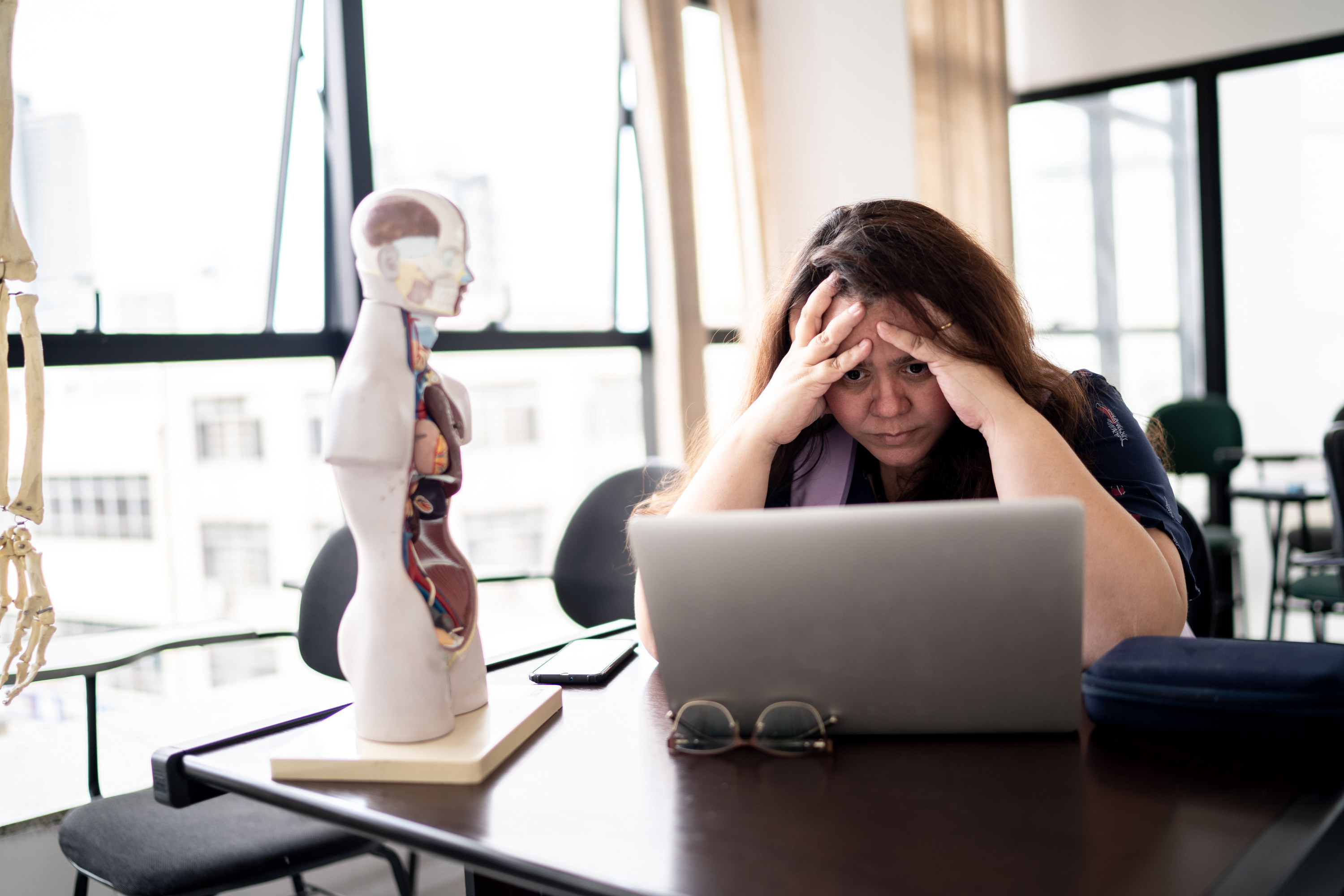 A stressed person holding their head in their hands as they look at their laptop
