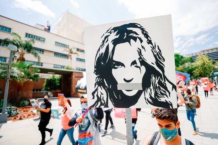 A Britney Spears fan holds up a sign that shows an illustration of the pop star with duct tape over her mouth