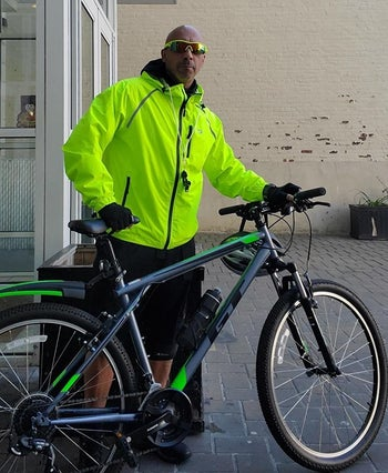 a reviewer wearing the jacket while holding his bike