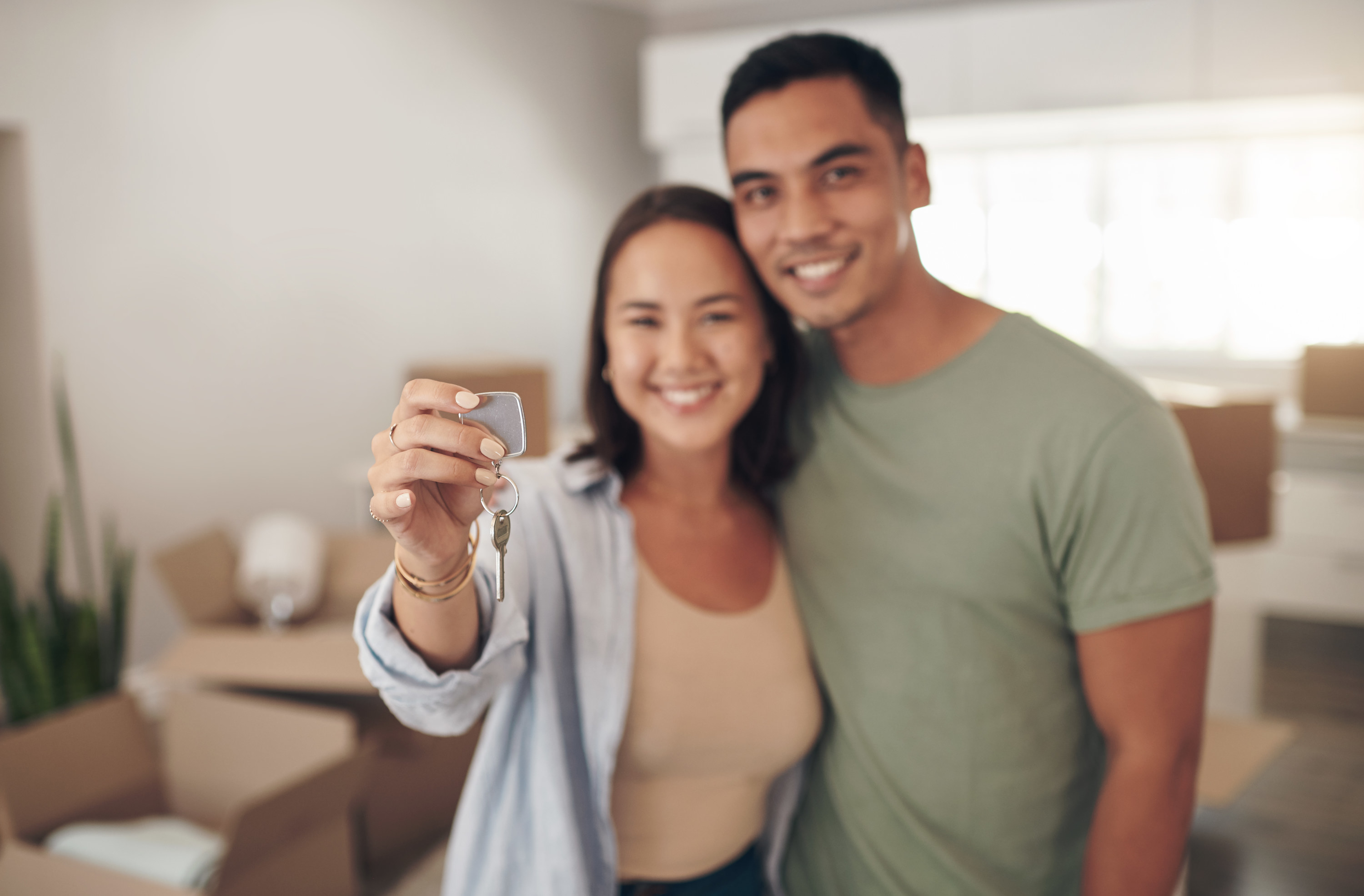 A couple holding up a key in their new home