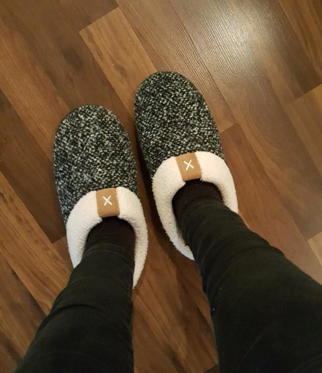 reviewer wearing a pair of grey, sherpa lined slippers