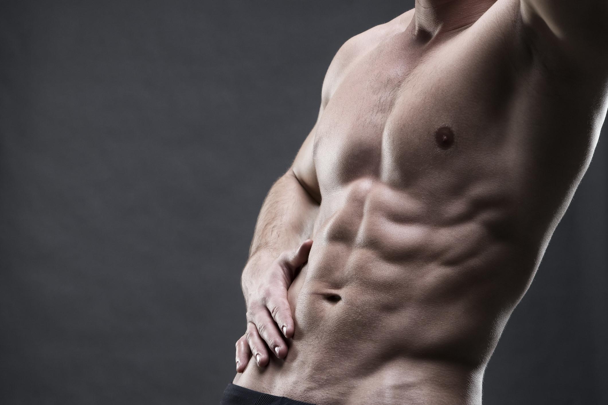 Handsome muscular bodybuilder posing on gray background